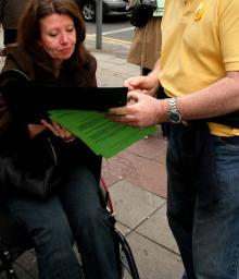Wheelchair user signing petition